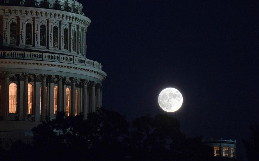 A full moon rises over the nation's capitol on Oct. 30, 2020, with the U.S. Capitol in the foreground. Government funding lapses at midnight on Friday, Dec. 18, 2020, and a partial, low-impact shutdown would ensue if Congress fails to pass a stopgap spending bill before then.