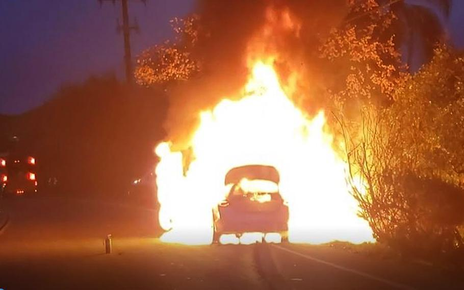 A vehicle burns after Marine Gunnery Sgt. Kyle Wetter rescued an 18-month-old child from it in Fallbrook, Calif., Dec. 7, 2020.
