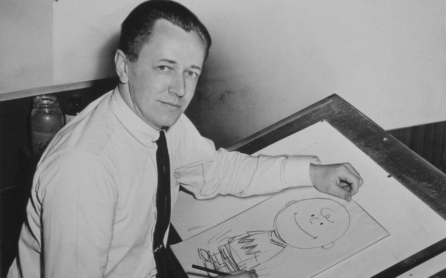 Charles M. Schulz sits at a drafting table with a drawing of Charlie Brown in 1956. Schulz, who served in the Army during World War II, created the comic strip Peanuts, which featured the characters Charlie Brown and Snoopy, among others.