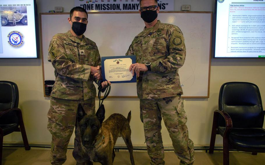 Brig. Gen. Larry Q. Burris Jr. presents Sgt. Michael Ramirez and Fritz, his military working dog, with Army Commendation Medals in Dec. 2020 for discovering a cache of unexploded bombs in Syria.