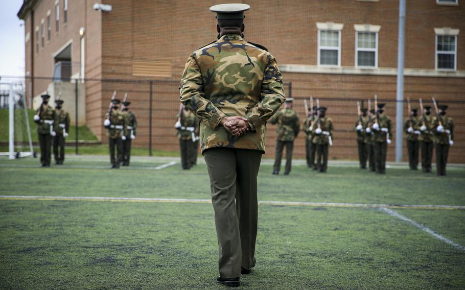 Marines with Marine Barracks Washington prepare in Washington, DC, Jan. 5, 2021, for the presidential nomination.  The Marines wear an unusual combination of a Vietnamese era field jacket in woodland camouflage with their khaki and olive green service uniforms.