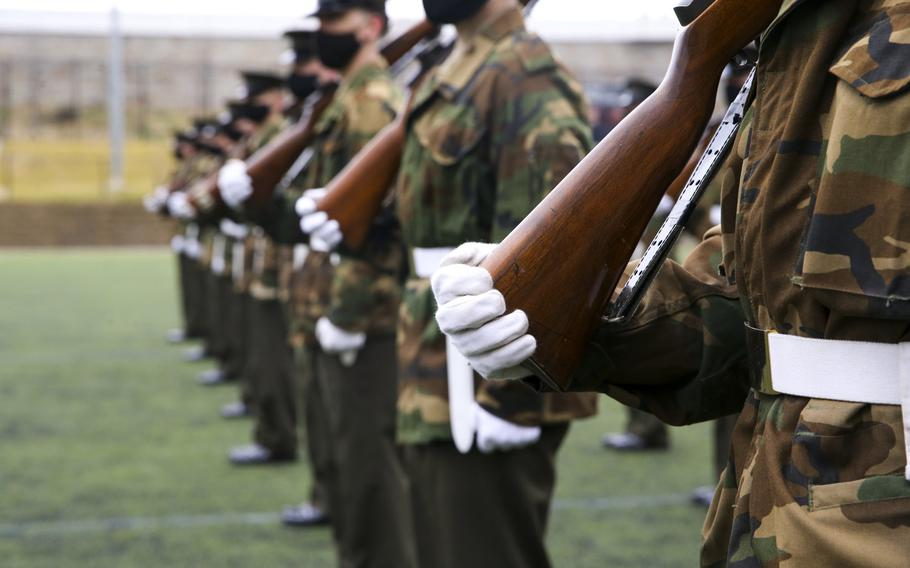 The Marines with Marine Barracks Washington are preparing in Washington, DC, Jan. 5, 2021, for the next presidential inauguration.  The Marines wear an unusual combination of a Vietnamese era field jacket in woodland camouflage with their khaki and olive green service uniforms.