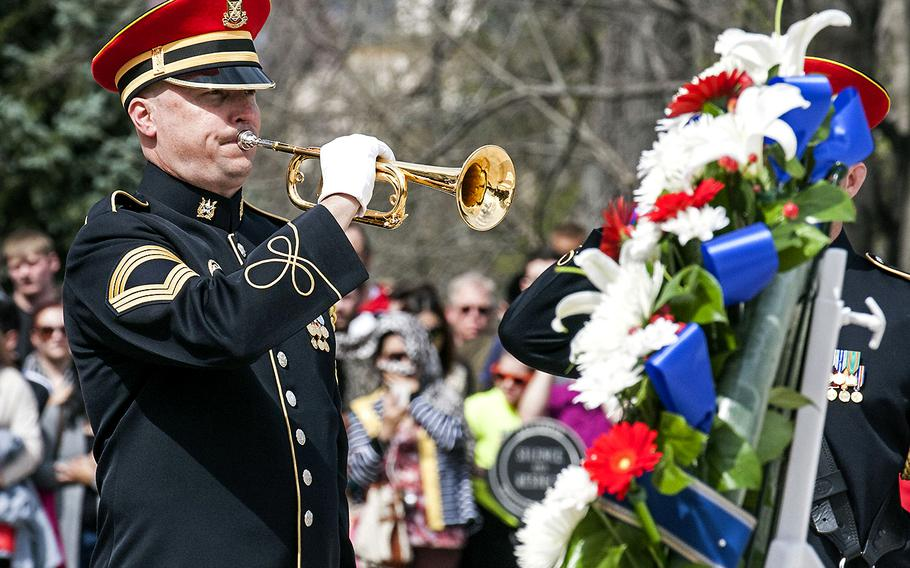 A service member plays taps during a wreath-laying ceremony at the Tomb of the Unknown Soldier in Arlington National Cemetery during Medal of Honor Day, March 25, 2016.