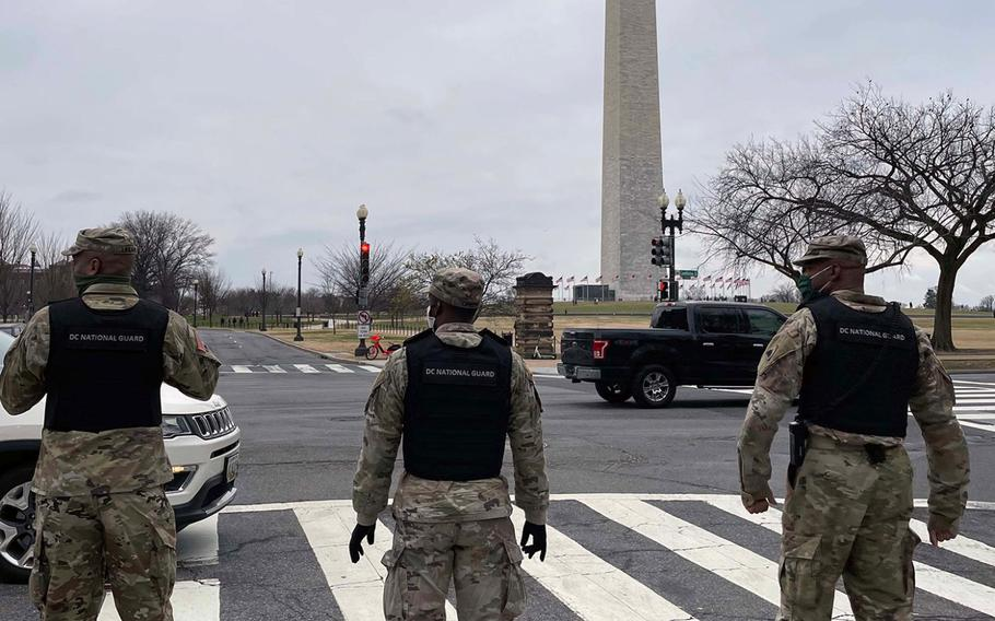 In a January 5, 2021 photo, DC National Guard members stand in front of the Washington Monument. The District of Columbia National Guard activated several hundred personnel to support the city government during expected demonstrations.