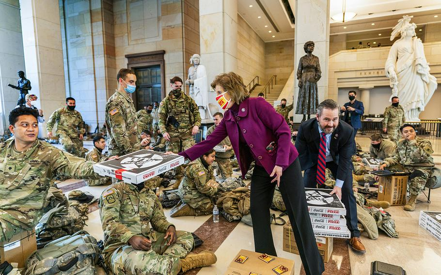 Rep. Vicky Hartzler, R-Mo., and Rep. Michael Waltz, R-Fla., hand pizzas to members of the National Guard gathered at the Capitol Visitor Center, Wednesday, Jan. 13, 2021, in Washington.