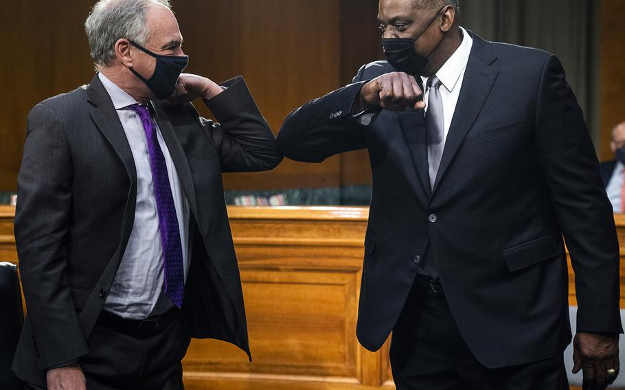 Secretary of Defense nominee Lloyd Austin elbow bumps Sen. Tim Kaine, D-Va., as he arrives for a confirmation hearing before the Senate Armed Services Committee on Capitol Hill, Tuesday, Jan. 19, 2021.