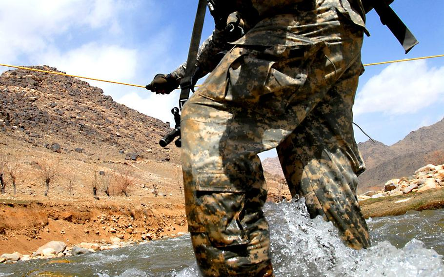 U.S. Army Spc. Nick Giovannelli from Bravo Company, 1st Battalion, 4th Infantry Regiment, fights the current as he crosses a river while on a dismount patrol mission near Forward Operation Base Baylough, Zabul Province, Afghanistan, on March 17, 2009. Giovanelli is suing to prevent retailers from selling Defense Department-released images of him.