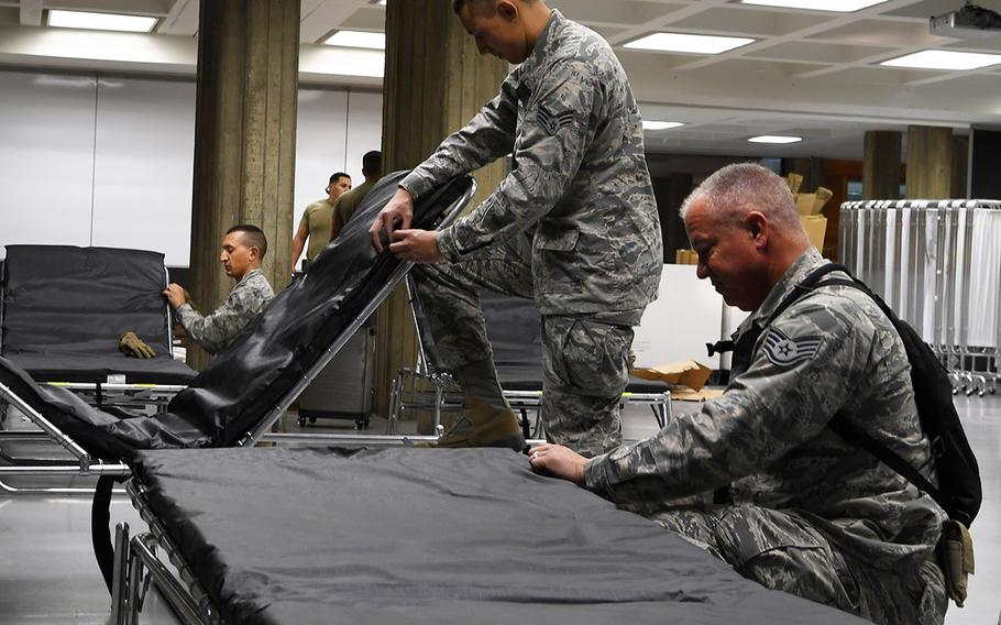 In an April 4, 2020 photo, airmen from the California Air National Guard's 146th Airlift Wing assemble cots at the Redding Civic Auditorium in Redding, California. This federal medical station (FMS) location was to have 100 general-use beds for patients from local hospitals experiencing overflow due to the coronavirus crisis.