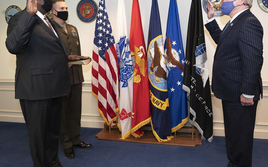 Washington Headquarters Services Director David Muir swears in Lloyd J. Austin III as secretary of defense at  the Pentagon, Jan. 22, 2021. Holding the BIble is the Junior Military Assistant to the Secretary of Defense, Marine Corps Lt. Col. Caleb Hyatt.