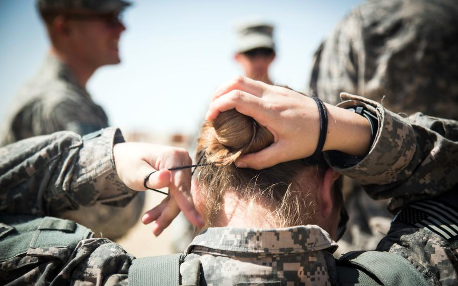 Spc. Nina Bray fixes her hair bun before putting on her body armor at a M203/M320 40 mm grenade launcher qualification range at Camp Buehring, Kuwait, March 17, 2014.