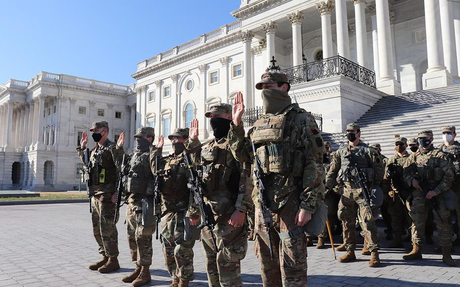 Five members of the Maryland National Guard's 1st Bn., 175th Infantry Regiment, reenlist outside the U.S. Capitol in Washington on Jan. 22, 2021. At least 25,000 Guard members, who were authorized to conduct security, logistical and communications missions leading up to and through the 59th Presidential Inauguration on Jan. 20, earned education benefits for the mission, a National Guard leader said Thursday, Jan. 28.