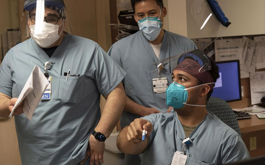 Army 1st Lt. Fernando Echeona, seated, speaks with lead nurse Manuel De La Cruz and charge nurse Stephen Joe while providing care to coronavirus patients during his shift in a telemetry department at the Adventist Health White Memorial Hospital in Los Angeles, on Jan. 22, 2021.