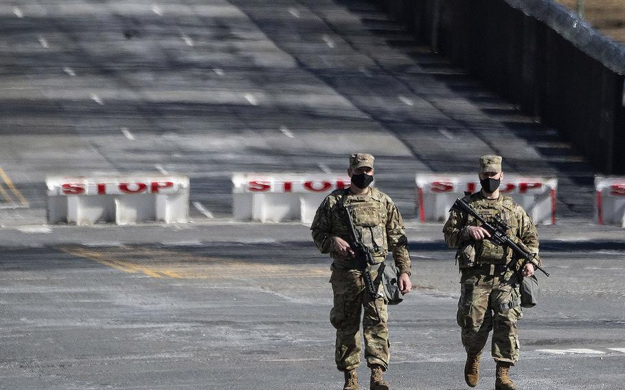 Two National Guard soldiers walk along Constitution Ave. near the U.S. Capitol on Feb. 4, 2020.
