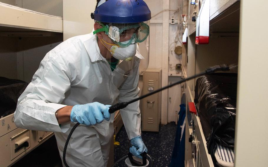 """Navy Aviation Electrician's Mate 3rd Class Kyle Hernandez, assigned to the """"Tomcatters"""" of Strike Fighter Squadron 31, disinfects a berthing aboard the aircraft carrier USS Theodore Roosevelt on April 12, 2020."""