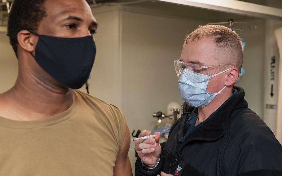 In a January 11, 2021 photo, a sailor on board the amphibious transport dock ship USS San Antonio receives the coronavirus vaccine.