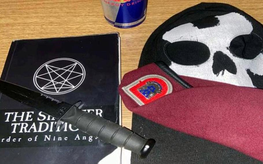 This photo seized from an iCloud account belonging to Army Pvt. Ethan Melzer by the Justice Department displays personal effects, including paraphernalia associated with the extremist group Order of the Nine Angles. Melzer is seeking to have federal charges based on him conspiring with extremist groups to ambush his unit dismissed.
