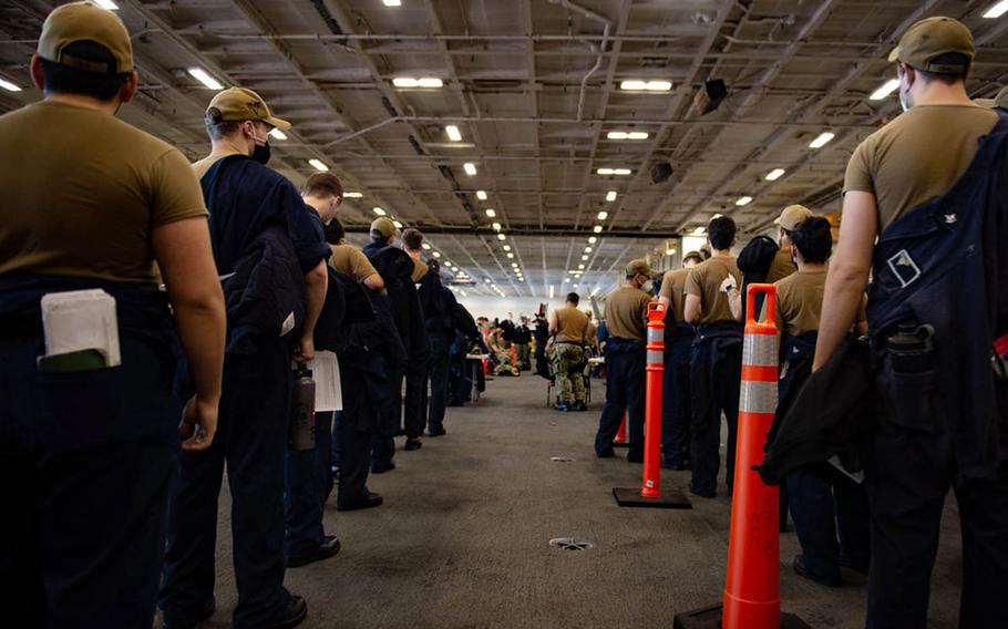 Sailors assigned to the USS Carl Vinson stand in line to receive the coronavirus vaccine, Friday, Feb. 19, 2021, while the aircraft carrier is docked in San Diego.