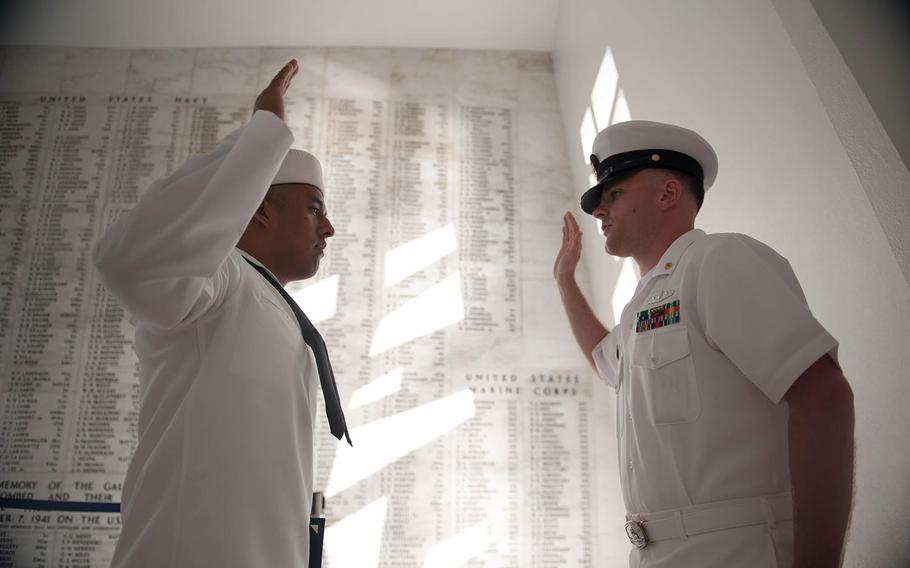 A sailor assigned to the guided-missile cruiser USS Mobile Bay recites the oath of enlistment inside the USS Arizona Memorial at Pearl Harbor, Hawaii, April 24, 2013.