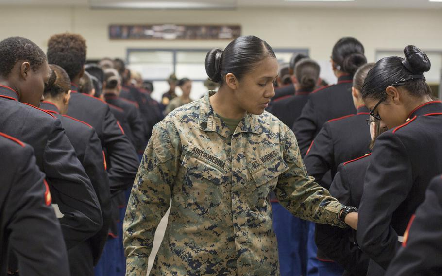 Sgt. Cristal Abregomedina examines the uniforms of Marines from the 4th Recruit Training Battalion in 2018 at Parris Island, S.C. Women in the military pay more out-of-pocket costs for uniform items than men, the Government Accountability Office found after Congress ordered a review.