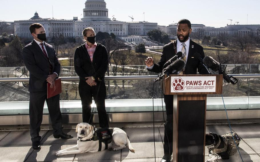 Veteran David Crenshaw, with his service dog Doc at his side, speaks at a Capitol Hill news conference to promote House bill, H.R. 1022, the Puppies Assisting Wounded Servicemembers (PAWS) Act, March 3, 2021. Behind him, left to right, are K9s For Warriors CEO: Rory Diamond and veteran Becca Stephens and her service dog Bobbi.