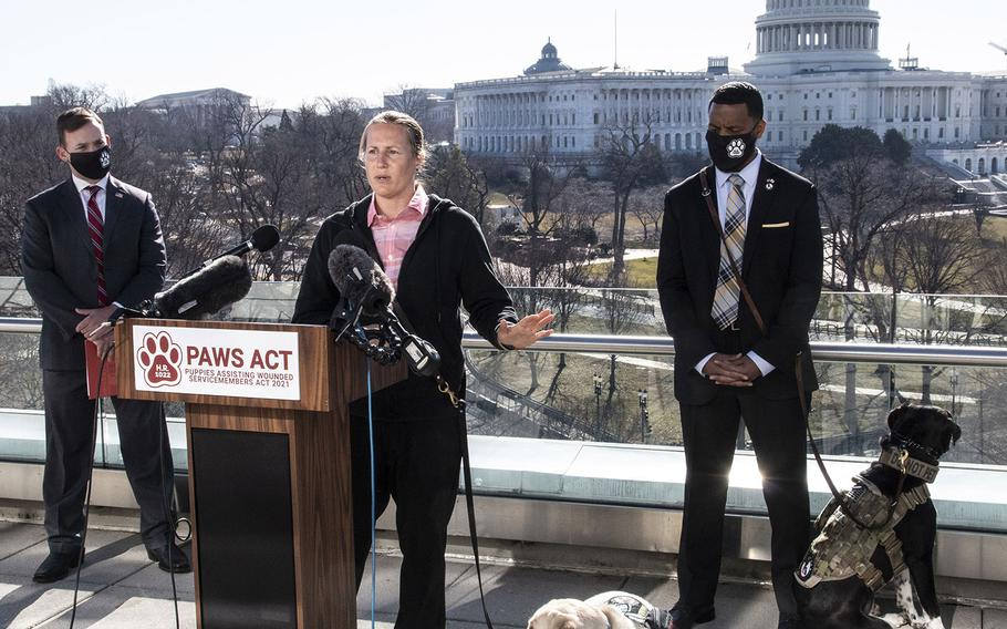 Veteran Becca Stephens, with her service dog Bobbi at her side, speaks at a Capitol Hill news conference to promote House bill, H.R. 1022, the Puppies Assisting Wounded Servicemembers (PAWS) Act, March 3, 2021. Behind her are K9s For Warriors CEO: Rory Diamond and veteran David Crenshaw and his service dog Doc