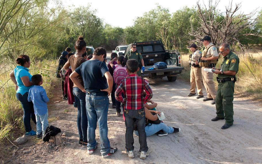 Border Patrol agents process a group of migrants apprehended near the border in this undated photo.
