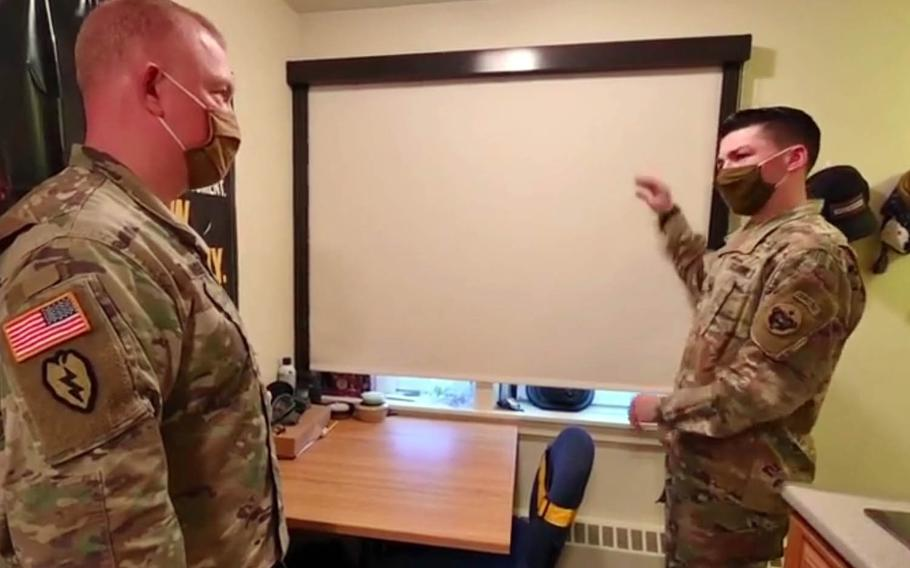 A soldier at Fort Wainwright, Alaska, talks about a blackout shade in his living quarters with Col. Adam Lange, deputy commander for sustainment for U.S. Army Alaska, in this video screenshot.