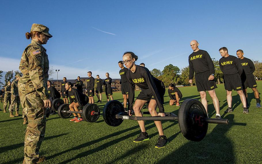 In an Oct. 23, 2018 photo, Army Staff Sgt. Jessica Smiley, a test grader with the Army's Center for Initial Military Training, looks on as soldiers with the 128th Aviation Brigade at Fort Eustis in Virginia demonstrate the deadlift, the first of six events of the new Army Combat Fitness Test.