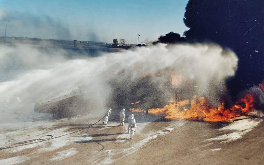 Air Force firefighters being covered in AFFF during training.