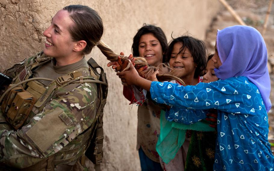 U.S. Army Sgt. Janean Sanders lets a group of Afghan girls play with her ponytail during a mission led by 25th Infantry Division soldiers in downtown Kandahar City, Afghanistan, in 2011. Sgt. Maj. of the Army Michael Grinston tweeted recently that long ponytails will be allowed with all uniforms. Currently, they are only allowed during physical training and with the Army Combat Uniform.
