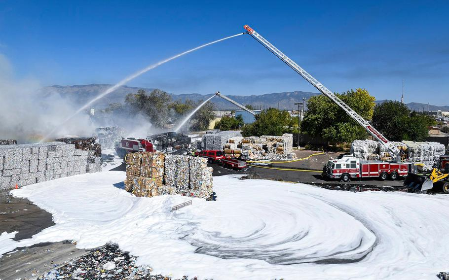 Kirtland Air Force Base firefighters spray foam to tamp down a recycling plant fire in Albuquerque, NM, on Sept. 29, 2020.