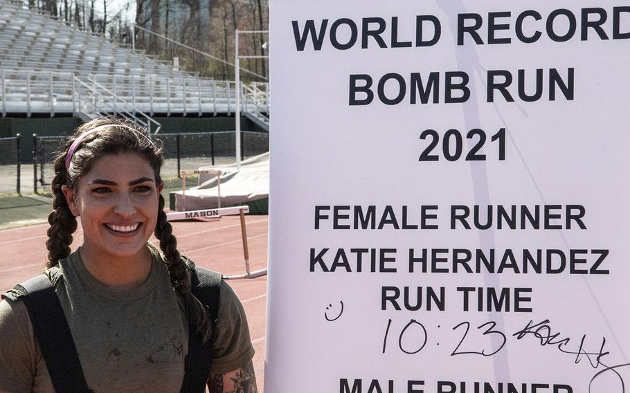 Army Capt. Katie Hernandez poses next to the finish-line banner after setting a world women's record for a mile run in a bomb disposal suit, Saturday, April 3, 2021, at George Mason University in Fairfax, Va.
