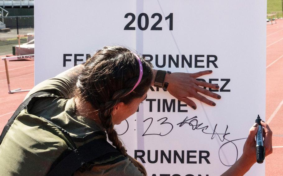 Army Capt. Katie Hernandez signs the finish-line banner after setting a world women's record for a mile run in a bomb disposal suit, Saturday, April 3, 2021, at George Mason University in Fairfax, Va.