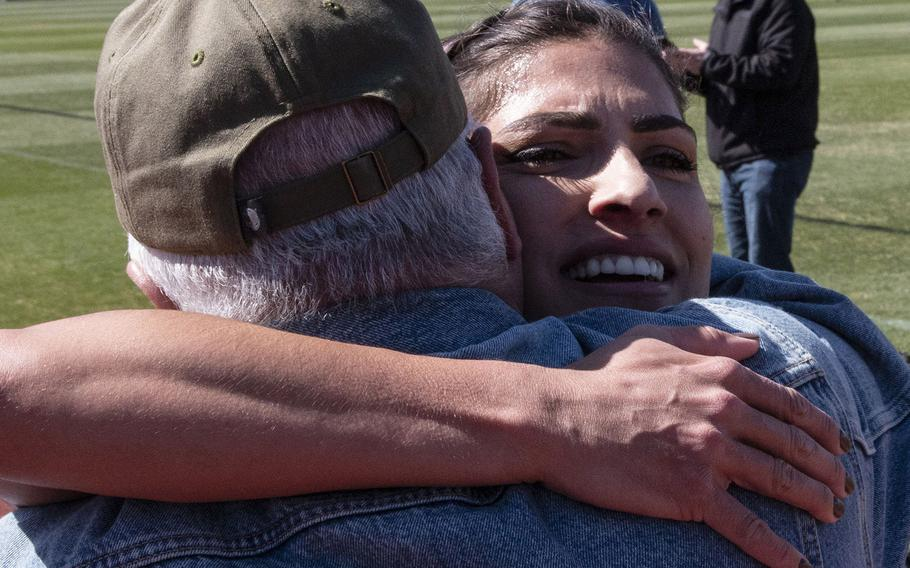 Army Capt. Katie Hernandez is congratulated by family members after setting a world women's record for a mile run in a bomb disposal suit, Saturday, April 3, 2021, at George Mason University in Fairfax, Va.