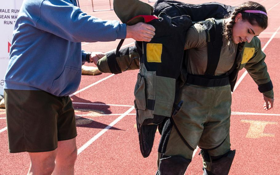 Army 1st Sgt. John Myers helps Capt. Katie Hernandez out of a bomb disposal suit after she set a world women's record for a mile run in the protective gear, Saturday, April 3, 2021, at George Mason University in Fairfax, Va.