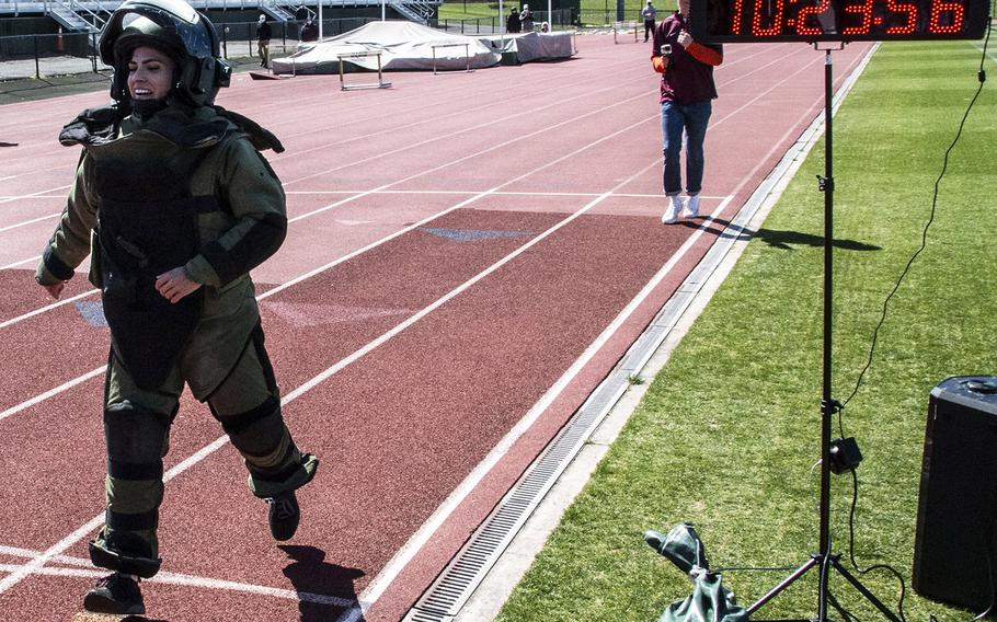 Army Capt. Katie Hernandez reaches the finish line with a world women's record for a mile run in a bomb disposal suit, Saturday, April 3, 2021, at George Mason University in Fairfax, Va.