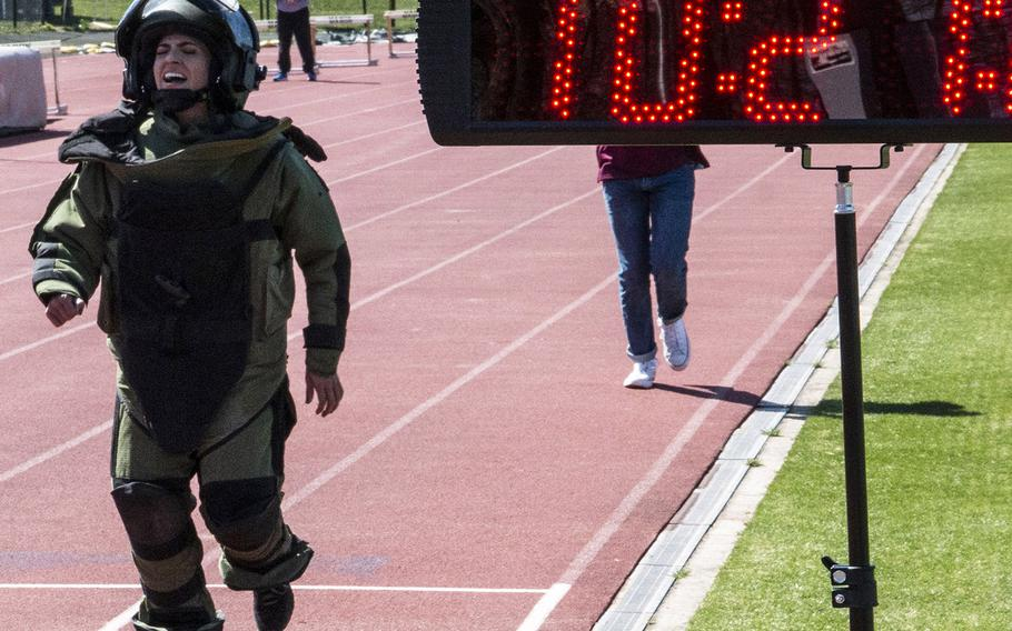 Army Capt. Katie Hernandez approaches the finish line with a world women's record for a mile run in a bomb disposal suit, Saturday, April 3, 2021, at George Mason University in Fairfax, Va.