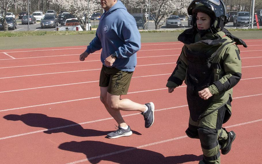 Paced by by Army 1st Sgt. John Myers, Capt. Katie Hernandez tries for the world women's record for a mile run in a bomb disposal suit, Saturday, April 3, 2021, at George Mason University in Fairfax, Va.