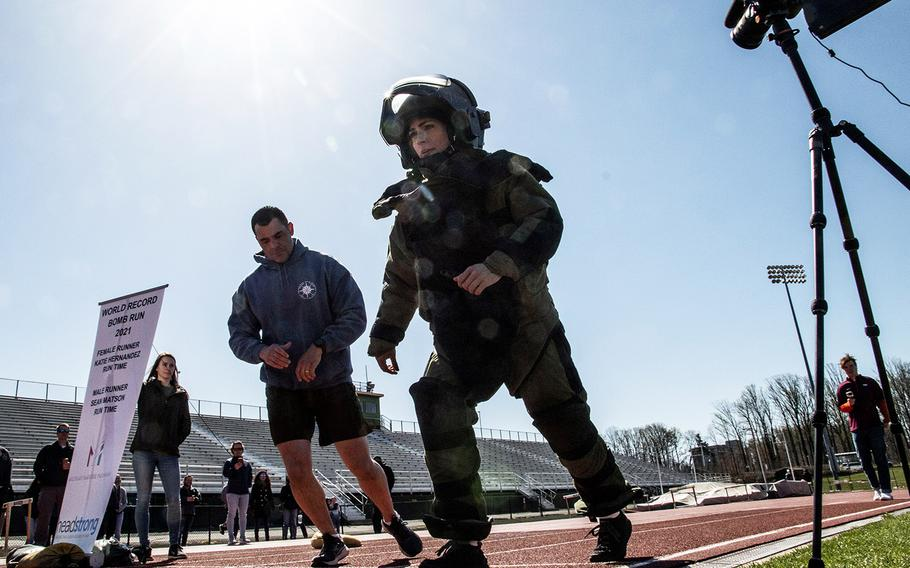 Paced by by Army 1st Sgt. John Myers, Army Capt. Katie Hernandez starts her quest for the world women's record for a mile run in a bomb disposal suit, Saturday, April 3, 2021, at George Mason University in Fairfax, Va.