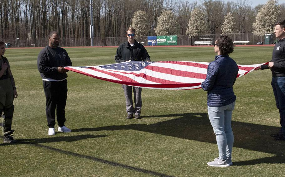 Army Capt. Katie Hernandez, left, stands for the playing of the national anthem before her attempt at a world women's record for a mile run in a bomb disposal suit, Saturday, April 3, 2021, at George Mason University in Fairfax, Va.
