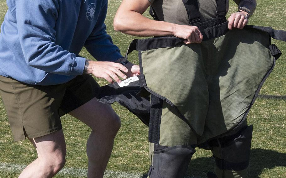 Army Capt. Katie Hernandez is helped into a bomb disposal suit by 1st Sgt. John Myers before her attempt at a world women's record for a mile run in the protective gear, Saturday, April 3, 2021, at George Mason University in Fairfax, Va.