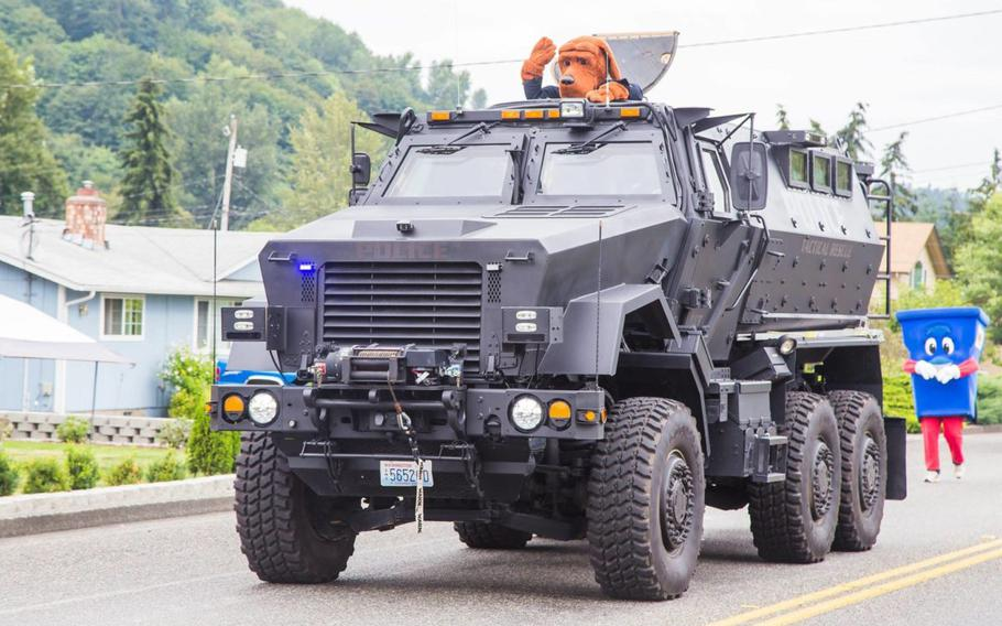 A surplus military mine-resistant armored personnel carrier drives down a street during a 2016 parade in Algona, Washington. The Snoqualmie Police Department acquired the vehicle as part of an equipment sharing program from the federal government. It is utilized by a coalition of small-city police departments.
