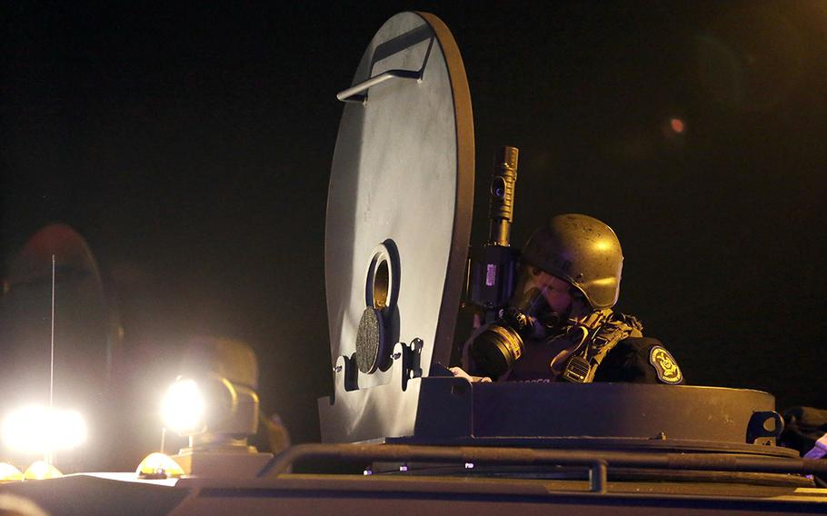 A member of the Missouri Highway Patrol is seen atop an armored personnel carrier in Ferguson, Mo., on Aug. 18, 2014. The Defense Department has transferred $7.4 billion in surplus military equipment to police in nearly all 50 states. House lawmakers on Tuesday, April 6, 2021, were urging President Joe Biden to prevent military weapons and other equipment such as grenades, grenade launchers and armored military vehicles from being provided to local police forces.