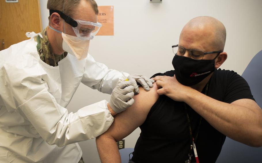 Capt. Aaron Sanborn injects Francis Holinaty on the first day of clinical testing of the Walter Reed Army Institute of Research's spike ferritin nanoparticle (SpFN) vaccine. Pre-clinical studies have found that SpFN induces highly potent  antibody responses against the virus that causes COVID-19 and three major variants.