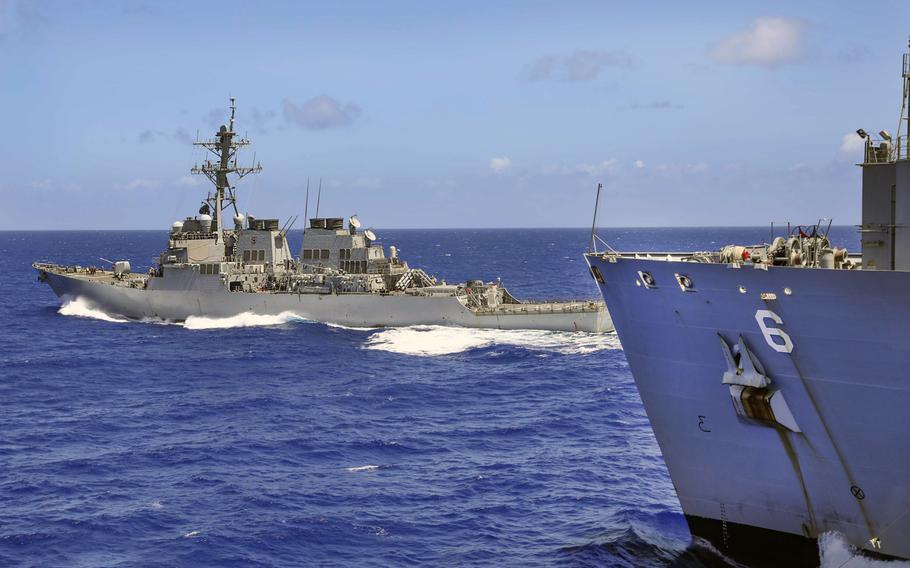 The destroyer USS John S. McCain breaks away from the dry cargo and ammunition ship USNS Amelia Earhart after a replenishment-at-sea in the Philippine Sea, March 26, 2021. Navy combat readiness has fallen in recent years due partly to limited maintenance capacity, a Government Accountability Office report found.