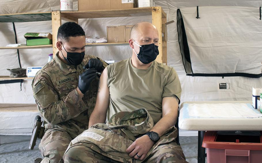 Sgt. Maj. John Shannon receives the COVID-19 vaccine from Sgt. Ryan Kamanu, a medic with the 466th Medical Company Area Support, at the the Role II medical facility at Al Asad Air Base, Iraq, on March 15, 2021.