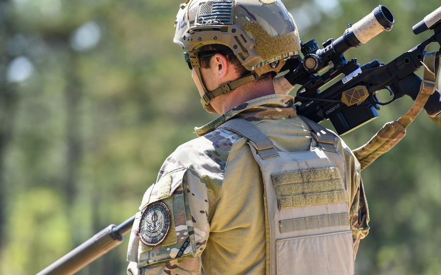 Coast Guard Petty Officer 2nd Class Randy Robinson, with the Maritime Security Response Team in Chesapeake, Virginia, totes a sniper rifle during the Army's Best Sniper Competition at Fort Benning, Ga., on Monday, April 12, 2021.