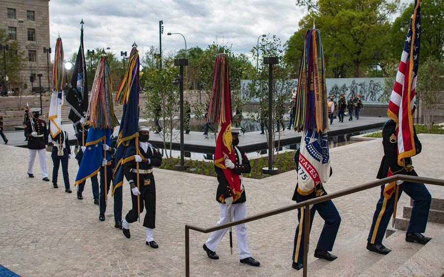 """Members of a military ceremonial honor guard march off followed by members of the U.S. Army Band """"Pershing's Own"""" at the conclusion of a dedication ceremony for the World War I Memorial in Washington, D.C. on Friday, April 16, 2021."""