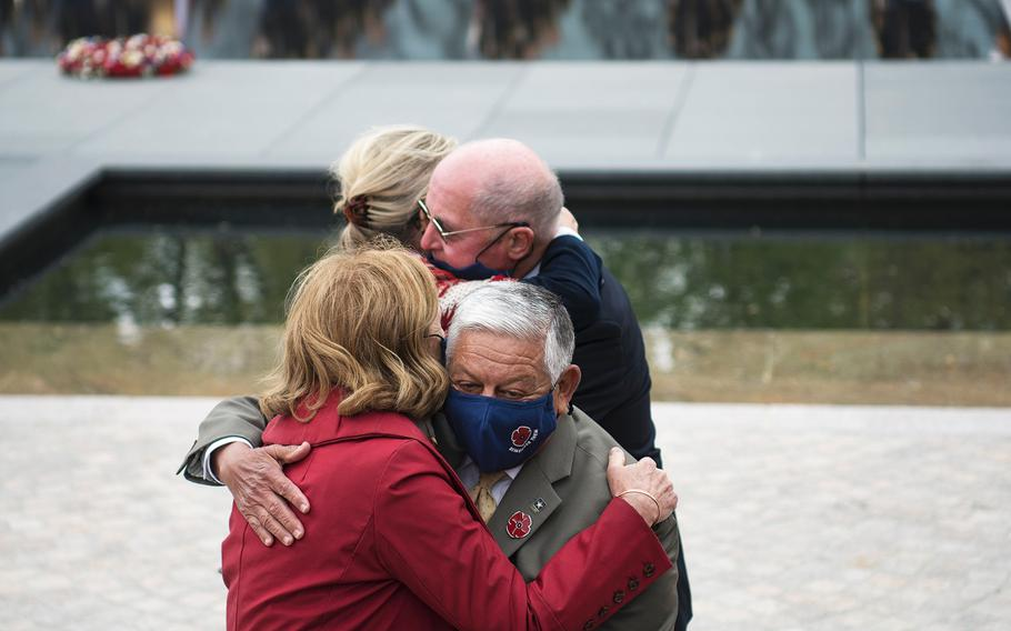 Dignitaries who were involved in promoting the new World War I Memorial hug each other at the conclusion of a dedication ceremony for the site on Friday, April 16, 2021, in Washington, D.C.