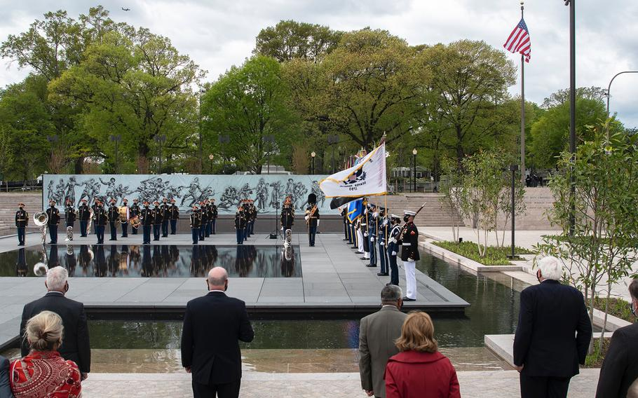 """Dignitaries who were involved in promoting the new World War I Memorial stand at attention in the foreground as a military honor guard and the U.S. Army Band """"Pershing's Own"""" take part in a dedication ceremony for the memorial in Washington, D.C., on Friday, April 16, 2021. In the background, the U.S. flag flies after it was raised for the first time at the site."""